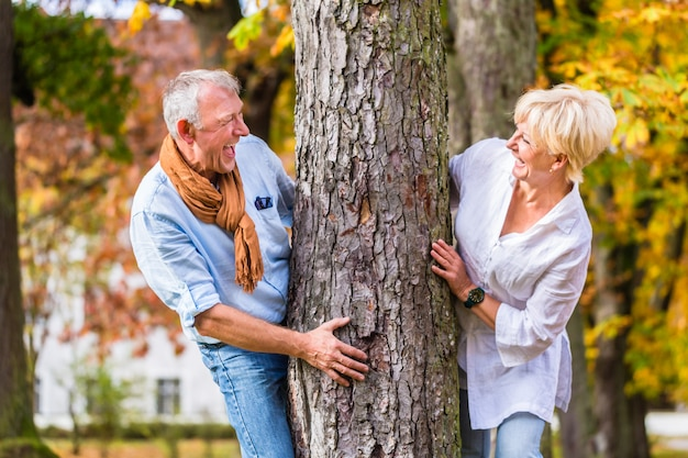 Coppie senior che flirtano giocando intorno all'albero in parco