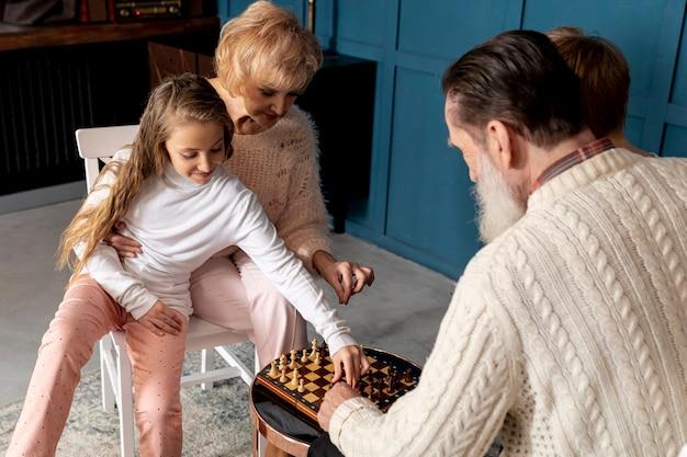 Coppie senior che giocano scacchi insieme ai loro nipoti