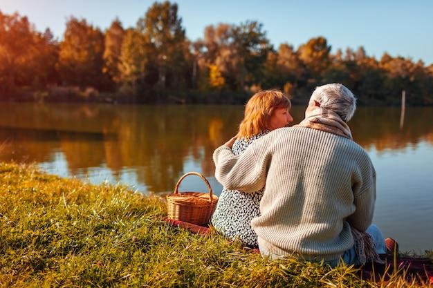 Coppie senior che hanno picnic dal lago di autunno abbracciare felice della donna e dell'uomo