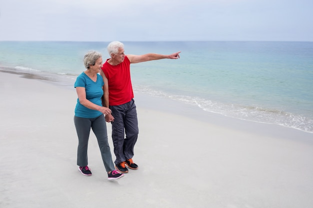 Coppie senior che parlano e che camminano sulla spiaggia