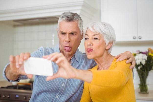 Coppie senior che prendono selfie dal telefono cellulare in cucina