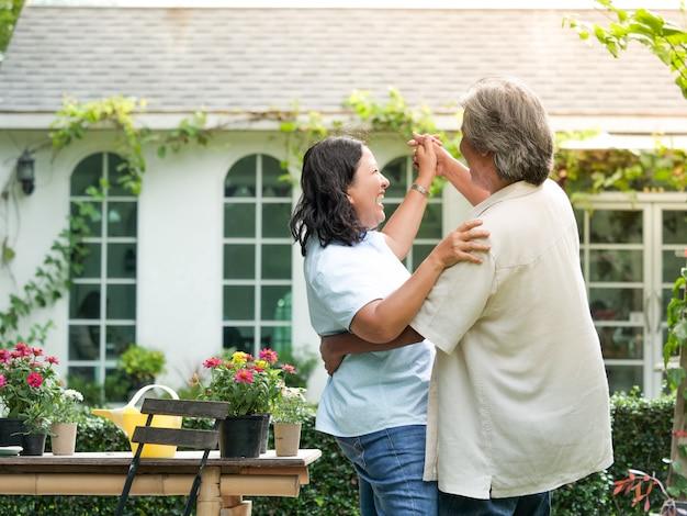 Coppie senior che ridono insieme nel giardino domestico.