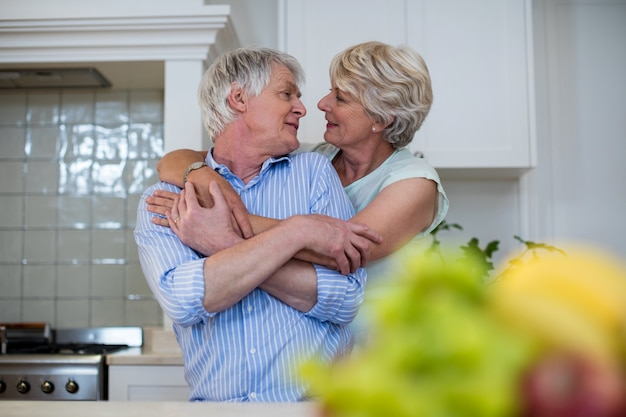 Coppie senior che si abbracciano in cucina