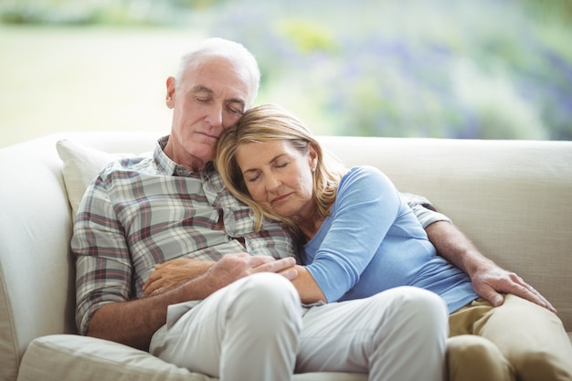 Coppie senior che si rilassano sul sofà in salone