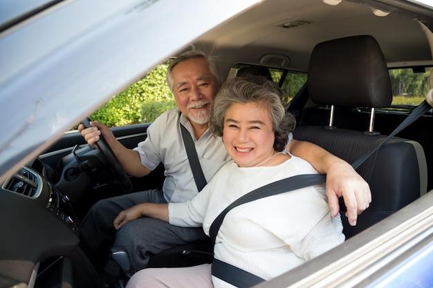 Coppie senior che si siedono dentro l'automobile che gode del viaggio e del sorridere soddisfatti del viaggio sulla strada, concetto maturo asiatico