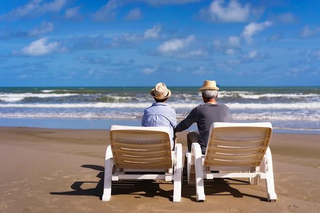 Coppie senior che si siedono sugli sdrai sulla spiaggia