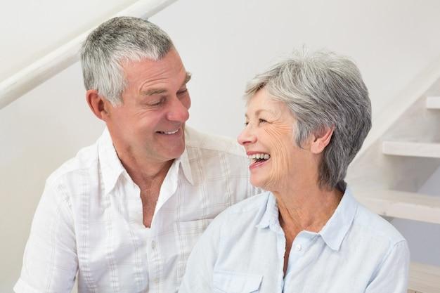 Coppie senior che si siedono sulle scale che sorridono a vicenda