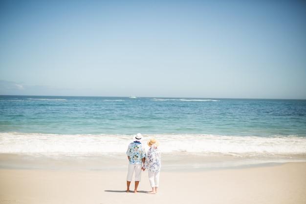 Coppie senior che si tengono per mano sulla spiaggia