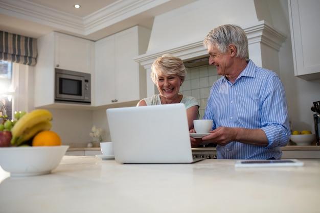Coppie senior che utilizzano computer portatile mentre mangiando tè nella cucina