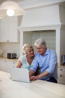 Coppie senior che utilizzano computer portatile nella cucina