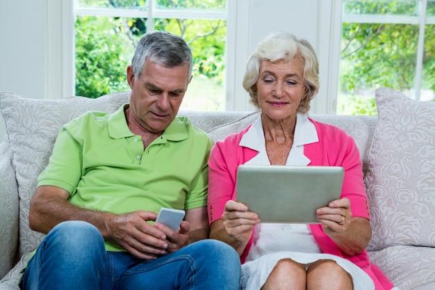 Coppie senior con la compressa digitale e telefono cellulare a casa