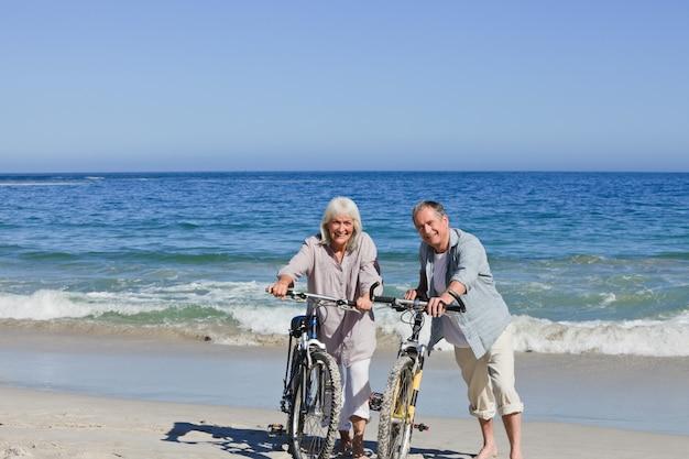 Coppie senior con le loro bici sulla spiaggia