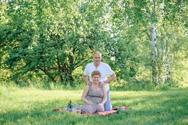 Coppie senior divertendosi insieme su un picnic nel parco.