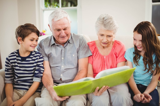 Coppie senior e loro nipoti che leggono un libro in salone