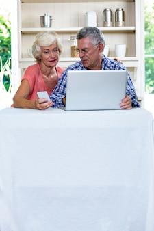 Coppie senior facendo uso del computer portatile e del telefono cellulare a casa