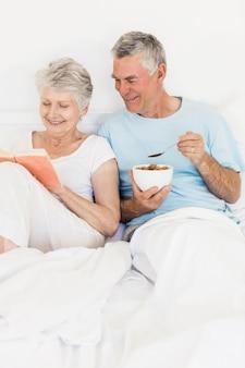 Coppie senior felici al letto che mangiano i cereali e libro di lettura