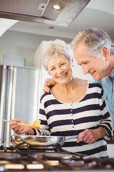 Coppie senior felici che cucinano alimento