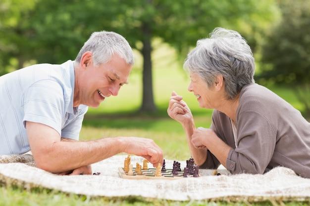 Coppie senior felici che giocano scacchi al parco
