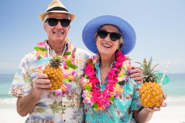 Coppie senior felici che indossano una ghirlanda e che tengono il cocktail dell'ananas