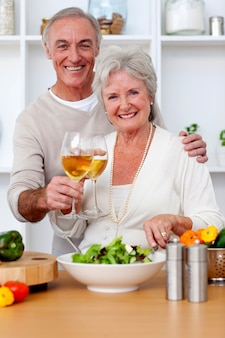 Coppie senior felici che mangiano un'insalata nella cucina