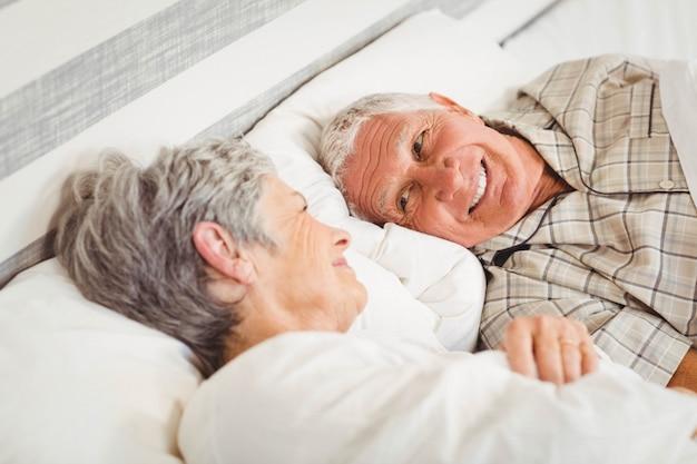 Coppie senior felici che ridono sul letto in camera da letto