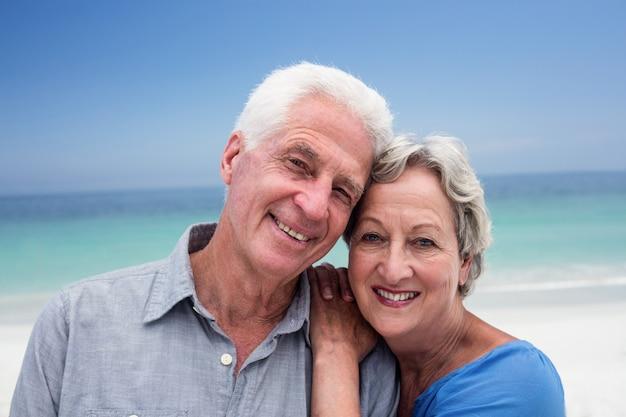 Coppie senior felici che si abbracciano sulla spiaggia