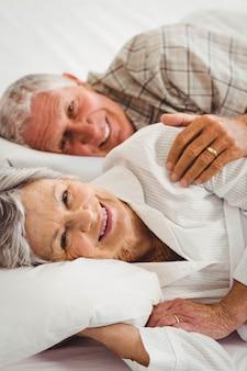 Coppie senior felici che si trovano sul letto in camera da letto