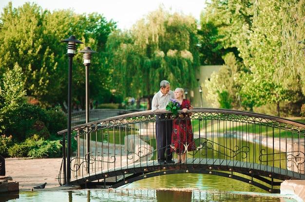 Coppie senior felici che stanno sul ponte vicino al fiume