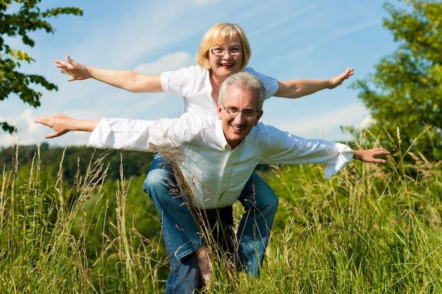 Coppie senior felici divertendosi all'aperto di estate