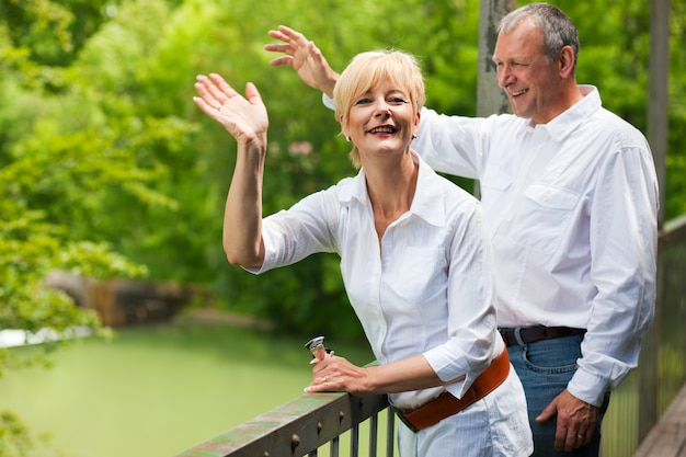 Coppie senior felici sulle mani d'ondeggiamento del ponte