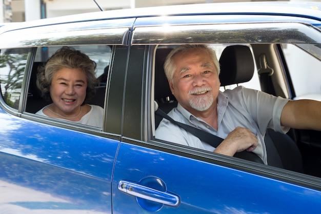 Coppie senior in automobile che godono del viaggio e del sorridere soddisfatti del viaggio sulla strada, concetto maturo asiatico