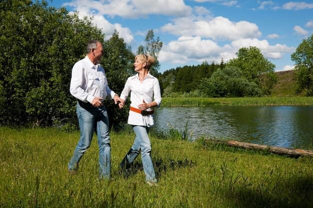 Coppie senior in un lago di estate
