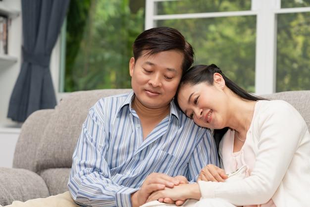 Coppie senior romantiche che si siedono insieme sul sofà a casa