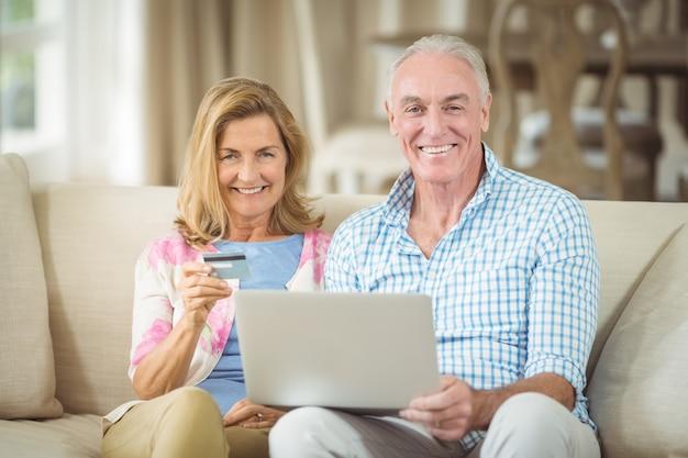 Coppie senior sorridenti che fanno spesa online sul computer portatile in salone