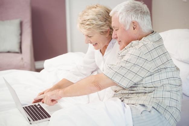 Coppie senior sorridenti che ridono mentre per mezzo del computer portatile