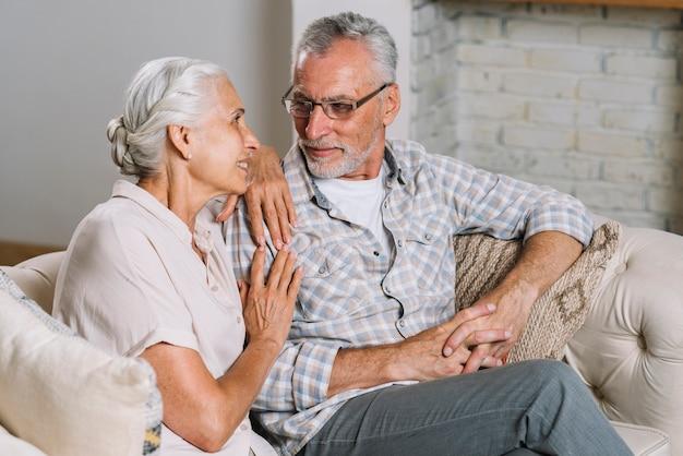 Coppie senior sorridenti che si siedono sul sofà che se lo esamina