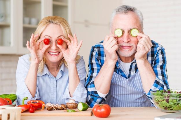 Coppie senior sorridenti che tengono i pomodori ciliegia e fette del cetriolo davanti ai loro occhi