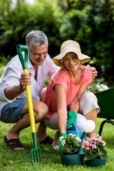 Coppie senior sorridenti con attrezzatura di giardinaggio all'iarda