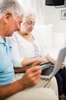 Coppie senior sorridenti facendo uso del computer portatile a casa