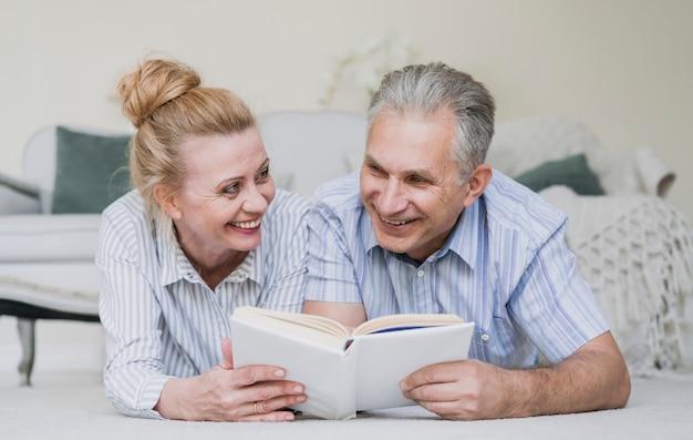 Coppie senior sveglie insieme ad un libro