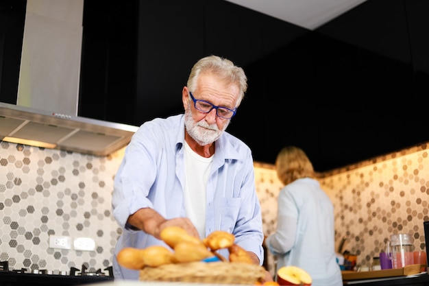 Coppie senior uomo e donna che cucinano nell'umore felice della cucina