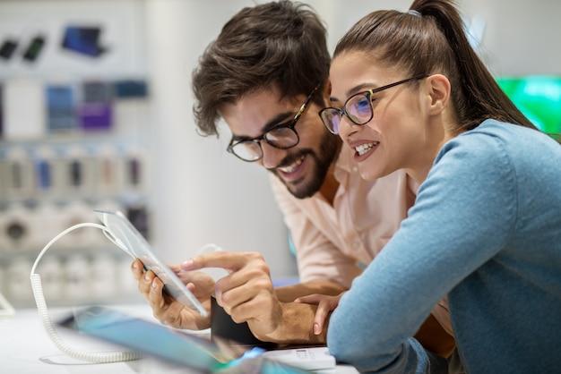 Coppie soddisfatte alla moda dei giovani pantaloni a vita bassa che collaudano il nuovo modello di un tablet nel negozio di tecnologia.