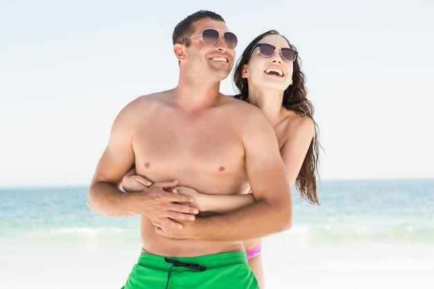 Coppie sorridenti che abbracciano sulla spiaggia