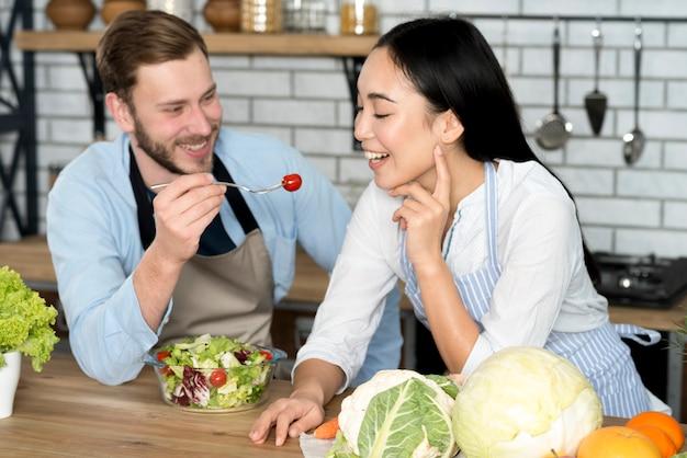 Coppie sorridenti che alimentano insalata sana in grembiule d'uso della cucina