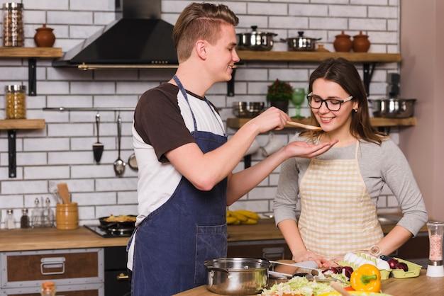 Coppie sorridenti che assaggiano alimento mentre cucinando insieme