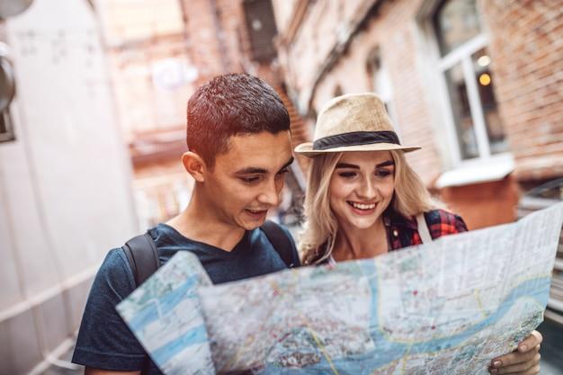 Coppie sorridenti che camminano sulla via con la mappa
