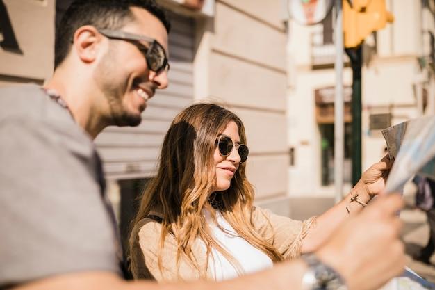 Coppie sorridenti che guardano mappa nella città