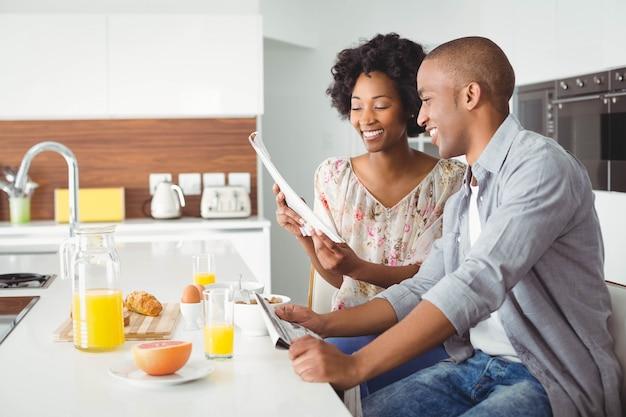 Coppie sorridenti che leggono insieme e che mangiano prima colazione nella cucina a casa