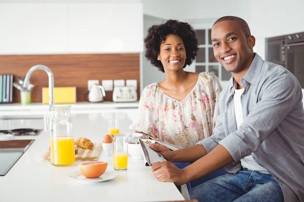 Coppie sorridenti che mangiano insieme prima colazione nella cucina a casa