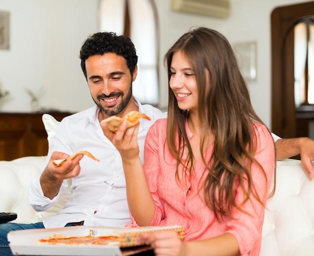 Coppie sorridenti che mangiano pizza mentre sedendosi sullo strato
